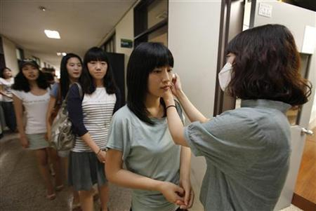 An assistant teacher checks a student's temperature before a class begins to prevent possible contagion of the H1N1 flu virus at Sangmyung University in Seoul August 28, 2009. REUTERS/Lee Jae-Won
