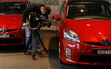 A cameraman works between two Prius at the Australian launching of the Toyota's new third-generation Hybrid Prius in central Sydney July 7, 2009. REUTERS/Daniel Munoz