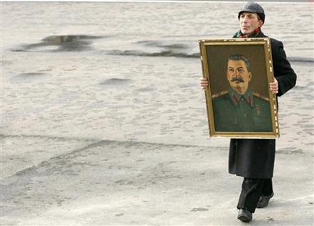 A man holding a portrait of Soviet dictator Josef Stalin walks at a rally marking Stalin's 128th birth anniversary in his hometown of Gori, some 80 km (50 miles) west of Tbilisi, December 21, 2007. REUTERS/David Mdzinarishvili