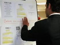 <p>A man looks at job postings at a job fair in New Hampshire in a file photo. REUTERS/Brian Snyder</p>