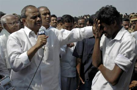 Chief Minister of Andhra Pradesh Y. S. Rajasekhara Reddy (L) comforts the relative of a victim of an overcrowded boat that capsized in the Krishna river in Mehboobnagar district, about 180 km southwest from Hyderabad January 19, 2007. REUTERS/Stringer/Files