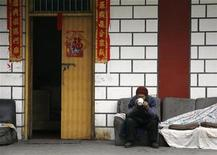<p>A man drinks tea as he sits outside his house adorned with Chinese New Year decorations in central Beijing March 4, 2009. REUTERS/David Gray</p>
