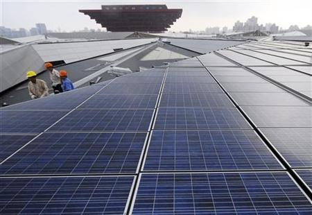 Workers are seen on a roof covered by solar panels at the Theme Pavilion of Shanghai World Expo 2010 in Shanghai August 23, 2009. REUTERS/China Daily
