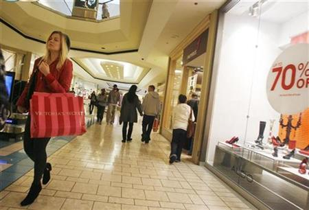 A woman walks with a shopping bag as shoppers buy gifts on Christmas Eve at the Beverly Center shopping mall in Los Angeles, California December 24, 2008. REUTERS/Fred Prouser