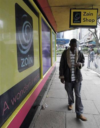 A man walk past a new mobile phone shop in Kenya's capital Nairobi in this July 31, 2008 file photo. REUTERS/Antony Njuguna/Files