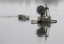 <p>Amateur inventor Tao Xiangli operates his homemade submarine in a lake on the outskirts of Beijing September 3, 2009. Tao, 34, made a fully functional submarine, which has a periscope, depth control tanks, electric motors, manometer, and two propellers, from old oil barrels and tools which he bought at a second-hand market. He took 2 years to invent and test the submarine which costs 30,000 yuan ($4,385). REUTERS/Christina Hu</p>