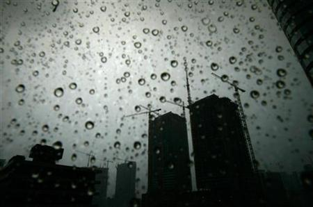Raindrops are seen on a window pane near cranes at the downtown area of Miami June 13, 2007. REUTERS/Carlos Barria