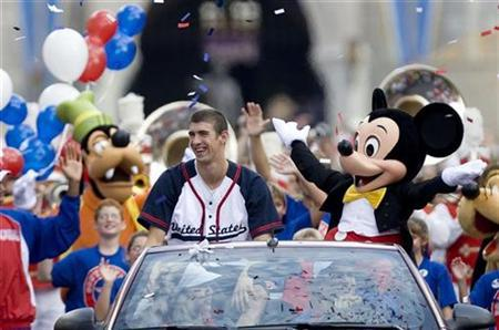 Olympic gold medal swimmer Michael Phelps rides down Main Street USA with Mickey Mouse during a parade at Walt Disney World's Magic Kingdom in Lake Buena Vista, Florida August 29, 2008. REUTERS/Scott Audette