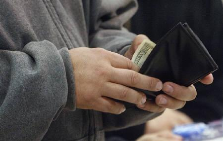 A shopper reaches into his wallet to pay for a purchase on ''Black Friday'' at the K-Mart store in Burbank, California in this November 28, 2008 file photo. REUTERS/Fred Prouser/Files