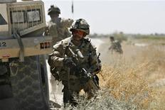 <p>Canadian Sgt.-Maj. Ivan Plante of Victoriaville, Quebec takes cover behind an armoured vehicle as gunfire breaks out at the scene of a roadside bomb explosion that wounded an Afghan National Army soldier in the Panjwai district of Kandahar province, September 14, 2009. REUTERS/Finbarr O'Reilly</p>
