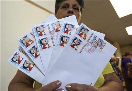 A woman holds envelopes with the Cuban Five postal stamps after the stamps' official launch in Havana September 12, 2007. REUTERS/Claudia Daut (CUBA)