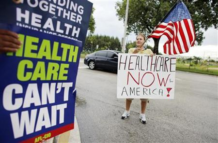 Supporters of the health care reform hold signs outside a health care town hall meeting with U.S. congressman Kendrick Meeks in Miami, Florida September 3, 2009. REUTERS/Carlos Barria