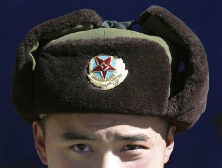 A Chinese soldier looks into the camera at the India-China trade route at Nathu-La, 55 km north of Gangtok, capital of Sikkim, January 17, 2009. REUTERS/Rupak De Chowdhuri/Files