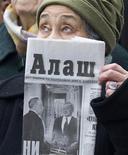 """<p>Женщина держит в руках газету во время митинга оппозиции в Алма-Ате 21 февраля 2009 года. Суд в Казахстане арестовал весь 23- тысячный тираж газеты """"Республика"""", счета собственника и издателя в обеспечение вердикта по иску подконтрольного властям банка, сообщила газета, назвав это предлогом для закрытия оппозиционного издания. REUTERS/Shamil Zhumatov</p>"""