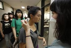 <p>An assistant teacher checks a student's temperature before a class begins to prevent possible contagion of the H1N1 flu virus at Sangmyung University in Seoul August 28, 2009. REUTERS/Lee Jae-Won</p>