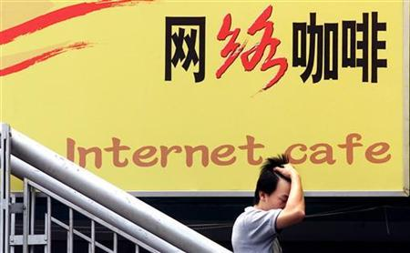 A Chinese man walks past a poster of a internet cafe in Beijing June 15, 2002. REUTERS/Guang Niu