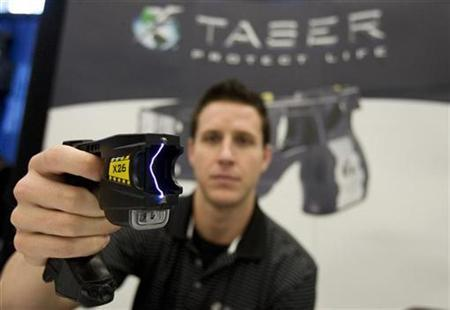Brian Black of Taser International demonstrates their X26 model at a trade show for the Canadian Association of Chiefs of Police in Montreal August 26, 2008. REUTERS/Christinne Muschi