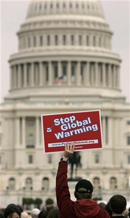 A protester holds up a placard during a Climate Change Protest in front of the U.S. Capitol in Washington, April 14, 2007. REUTERS/Hyungwon Kang