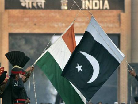 Pakistani Rangers and Indian Border Security Force personnel (obscured) lower the flags of the two countries during a daily flag lowering ceremony at the India-Pakistan joint border at Wagah in this December 14, 2006 file photo. REUTERS/Mian Khursheed/Files