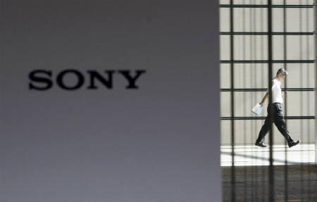 A man is seen behind a logo of Sony Corp at its headquarters in Tokyo July 30, 2009. Sales of the PlayStation 3 video game console jumped in the weeks after a $100 price cut last month, and strong demand could lead to empty shelves at retail, a Sony Corp executive said on Wednesday. REUTERS/Kim Kyung-Hoon/Files