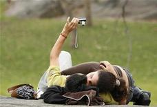 <p>A couple share a kiss as they take their own photograph during a warm spring day in Central Park in New York April 2, 2009. REUTERS/Lucas Jackson</p>