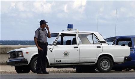 A Cuban policeman stands by a Russian-built Lada patrol car on Havana's seafront ''El Malecon'' boulevard, in this September 23, 2009 file photo. REUTERS/Desmond Boylan