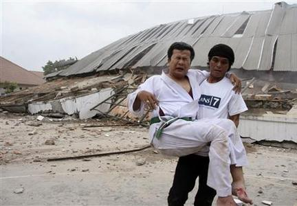 A man carries an injured person in front of a collapsed university building during an evacuation after an earthquake hit Padang, on Indonesia's Sumatra island September 30, 2009. REUTERS/Muhammad Fitrah/Singgalang Newspaper