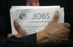 <p>A man carrying a stack of job listings listens to a discussion at the One Stop employment center in San Francisco, California, August 12, 2009. REUTERS/Robert Galbraith</p>