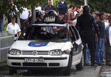 <p>Policiais e torcedores observam atrás de carro destruído em Siroki Brijeg. Um torcedor foi morto e 22 pessoas, incluindo 12 policiais, ficaram feridas em confrontos antes de uma partida válida pela primeira divisão do Campeonato Bósnio neste domingo, na cidade de Siroki Brijeg, na região Sudoeste do país, segundo informações da polícia.04/10/2009.REUTERS/Stringer</p>