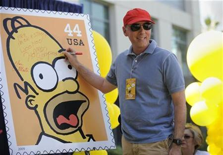 Dan Castellaneta, the voice of Homer Simpson, signs a poster at the unveiling of the new ''The Simpsons'' U.S. postage stamps in Los Angeles May 7, 2009. REUTERS/Phil McCarten