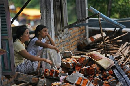 Survivors sit inside their damaged house after an earthquake occured near the Padang Alai village area in Pariaman, West Sumatra province October 6, 2009. REUTERS/Nicky Loh