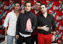 """<p>La banda mexicana Panda posa con su premio MTV Latino en Ciudad de México, 5 oct 2009. El grupo mexicano Panda, elegido anoche mejor artista de la región norte por la cadena MTV Latino, criticó la decisión del canal de música de premiarlos en un evento local, ajeno a la gala central que tendrá lugar en Los Angeles, Estados Unidos. La banda de punk pop, que cuenta ya con seis de los galardones en forma de lengua que el canal otorga anualmente, calificó de """"compleja y complicada"""" la nueva modalidad para entregar el premio en su edición 2009. REUTERS/Daniel Aguilar</p>"""