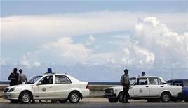 <p>Policías cubanos cerca de sus vehículos Lada (der) y Geely (izq) en El Malecón, 23 sep 2009. Lada, el austero coche soviético de los funcionarios en Cuba, ve acercarse peligrosamente por el retrovisor al primer rival en 30 años: otro automóvil socialista, pero con aire acondicionado. Ministros, dirigentes y policías cubanos están cambiando el rígido volante de sus Lada por la dirección asistida del moderno Geely CK chino, símbolo de una nueva alianza con Pekín, hoy el segundo socio comercial de Cuba. Pero el Lada, un automóvil de líneas rectas y rústicas terminaciones inspirado en el Fiat 124 de la década de 1960, se transformó en un objeto de culto en Cuba. REUTERS/Desmond Boylan</p>