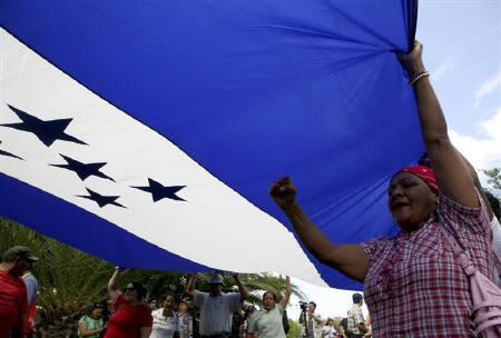 Supporters of Honduras' ousted President Manuel Zelaya hold a giant Honduras flag during a protest outside the hotel where members of the Organization of American States (OAS) mission are staying in Tegucigalpa October 8, 2009. REUTERS/Oswaldo Rivas
