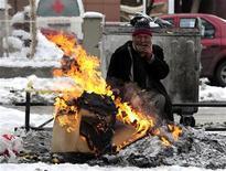 <p>Un senzatetto si riscalda per strada. REUTERS/Ognen Teofilovski</p>