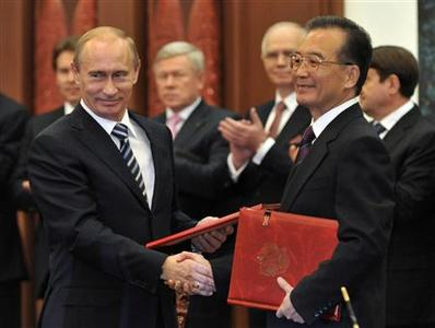 Russian Prime Minister Vladimir Putin and Chinese Premier Wen Jiabao shake hands after signing a bilateral cooperation agreement at the Great Hall of the People in Beijing, October 13, 2009. REUTERS/Kyodo/Kota Kyogooku/Pool