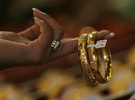 A woman buyer looks at gold bangles at a jewellery shop in Mumbai October 8, 2009. REUTERS/Arko Datta