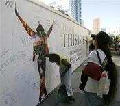 """<p>Mulher assina mural em tributo a Michael Jackson em Los Angeles. As vendas antecipadas de """"This Is It"""" prenunciam que o filme-show com o falecido astro Michael Jackson será uma das maiores bilheterias da história.25/09/2009.REUTERS/Danny Moloshok</p>"""