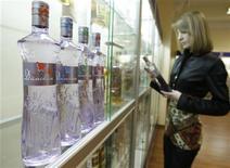 <p>Женщина рассматривает бутылку водки в Санкт-Петербурге 14 марта 2008 года. Настроение российских потребителей стало улучшаться, хотя 80 процентов жителей страны экономят на покупке повседневных товаров, не жалея средств на водку, констатирует международное аналитическое агентство Nielsen. REUTERS/Alexander Demianchuk</p>