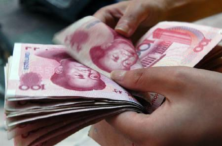 A shop assistant checks hundred yuan bank notes at a shop in Xiangfan, central China's Hubei province, in this August 2006 file photo. REUTERS/Stringer