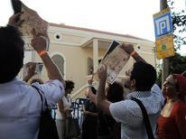 """<p>Israelíes sostienen mapas de dos caras durante un recorrido vistual de Gaza en Tel Aviv. Itai Shimon se queda paralizado, con su teléfono móvil presionado contra su oreja, escuchando las descripciones de un enorme cráter de escombros que alguna vez fue un estadio para 10.000 personas en la Franja de Gaza. """"Entremos por las puertas del estadio nacional de fútbol y el hogar del equipo palestino. Una noche en abril del 2006, el estadio fue bombardeado por aviones de combate israelíes"""", dice una voz por el celular. Pero Shimon no está en Gaza. Se encuentra en Tel Aviv en un """"meta-recorrido"""" del enclave palestino con You Are Not Here (YANH), una """"plataforma para el turismo urbano"""" que ofrece giras virtuales con audio de ciudades en zonas de conflicto con el objetivo de fomentar la comprensión. REUTERS/YANH/Handout</p>"""