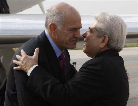 Greek Prime Minister George Papandreou (L) greets Cypriot President Demetris Christofias as he arrives during his state visit to the east Mediterranean island, in Larnaca October 19, 2009. The two leaders met to discuss Turkey's prospects of entering the EU and their bilateral relations. REUTERS/Andreas Manolis