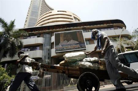 Workers pull a hand-cart in front of the Bombay Stock Exchange (BSE) building in Mumbai May 19, 2009. REUTERS/Punit Paranjpe/Files