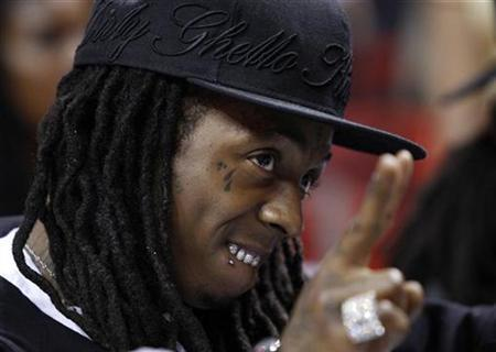 Rap recording artist Lil Wayne watches the Miami Heat play the Atlanta Hawks in Game 4 of their NBA Eastern Conference playoff series in Miami, Florida April 27, 2009. REUTERS/Hans Deryk