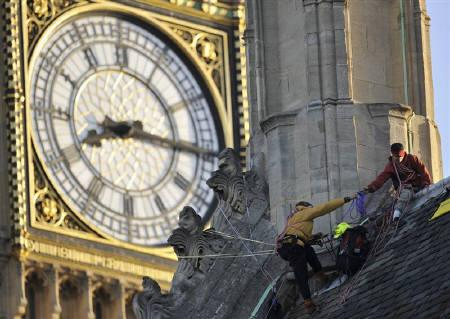 Environmental protestors are seen on the roof of the Palace of Westminster in London October 12, 2009. As Britain prepares to put the clocks back this weekend, one of its leading historians has called for the UK to join the same time zone as the rest of Europe -- and leave Scotland in the dark. REUTERS/Kieran Doherty/Files