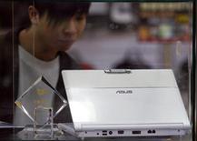 <p>Un ragazzo guarda un laptop della Asustek nella vetrina di un negozio di elettronica di Taipei. REUTERS/Nicky Loh</p>