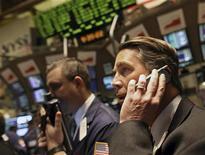 <p>Brocker lavorano col cellulare alla Borsa di New York. REUTERS/Brendan McDermid</p>