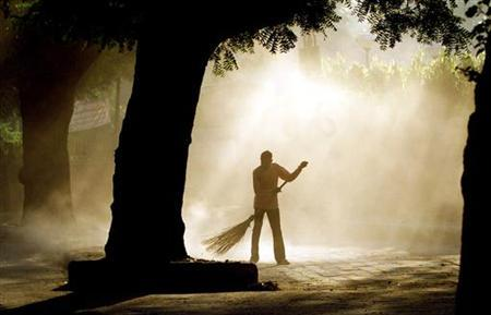 An Indian sweeper cleans a street in early morning in New Delhi in this file photo from October 3, 2003. REUTERS/B Mathur