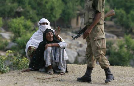Pashtun women ask a soldier to help them flag down transport in Buner district near Islamabad in this June 2009 file photo. Thousands of civilians in northwest Pakistan need protection from fighting between government forces and Taliban militants and dozens are being injured by shelling every day, aid workers say. REUTERS/Faisal Mahmood