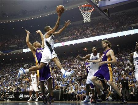 Orlando Magic guard Rafer Alston goes over Los Angeles Lakers guard Derek Fisher to score in the first quarter, as Magic's Dwight Howard (2nd R) and Lakers Pau Gasol (R) watch, during Game 4 of their NBA Finals basketball game in Orlando, Florida, June 11, 2009. REUTERS/Jeff Haynes